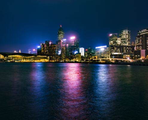 Hong Kong city by night skyscrapers, water reflection, blue sky, Artur Rydzewski photography