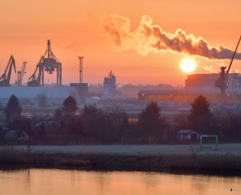 Szczecin o wschodzie słońca Stettin sun rise smoke orange water river odra